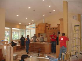Residential Remodeling. Electricians talking with owner, measuring, and installing lights.