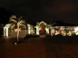 Landscape Lighting. Residential home front view with nicely lit trees, plants, and home at night.